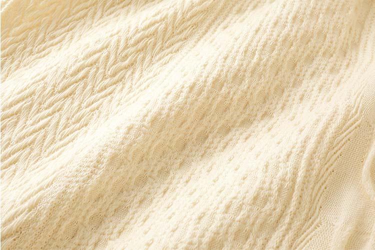 編み柄がスカート全体にほどこされているのでアイボリーは華やかな印象に。
