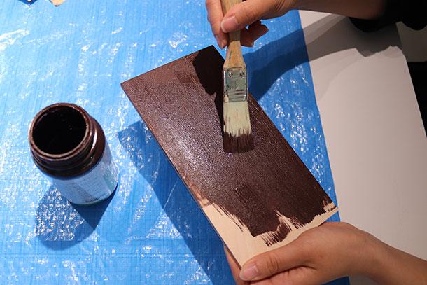 刷毛を使って板を塗装します