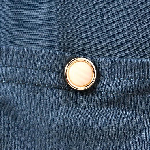 視線を上に引き上げるゴールド遣いのボタンがアクセントに。