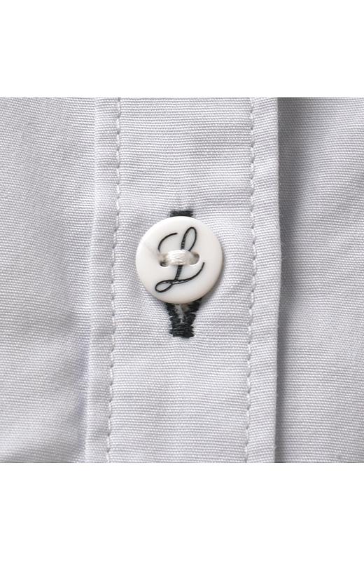 第三ボタンとカフスは、胸もとの刺しゅうと同じ「L」をデザインしたオリジナルボタン。