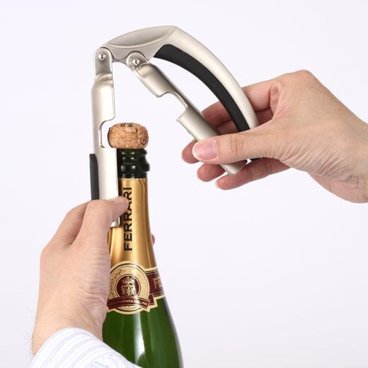 これは参考画像です。シャンパンオープナーを開き、くぼみにコルクを挟み込みます。
