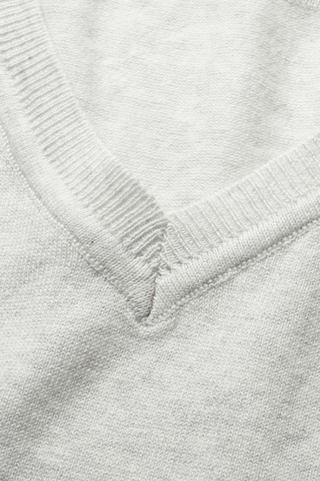 編地に変化をつけた衿もとがポイントに。
