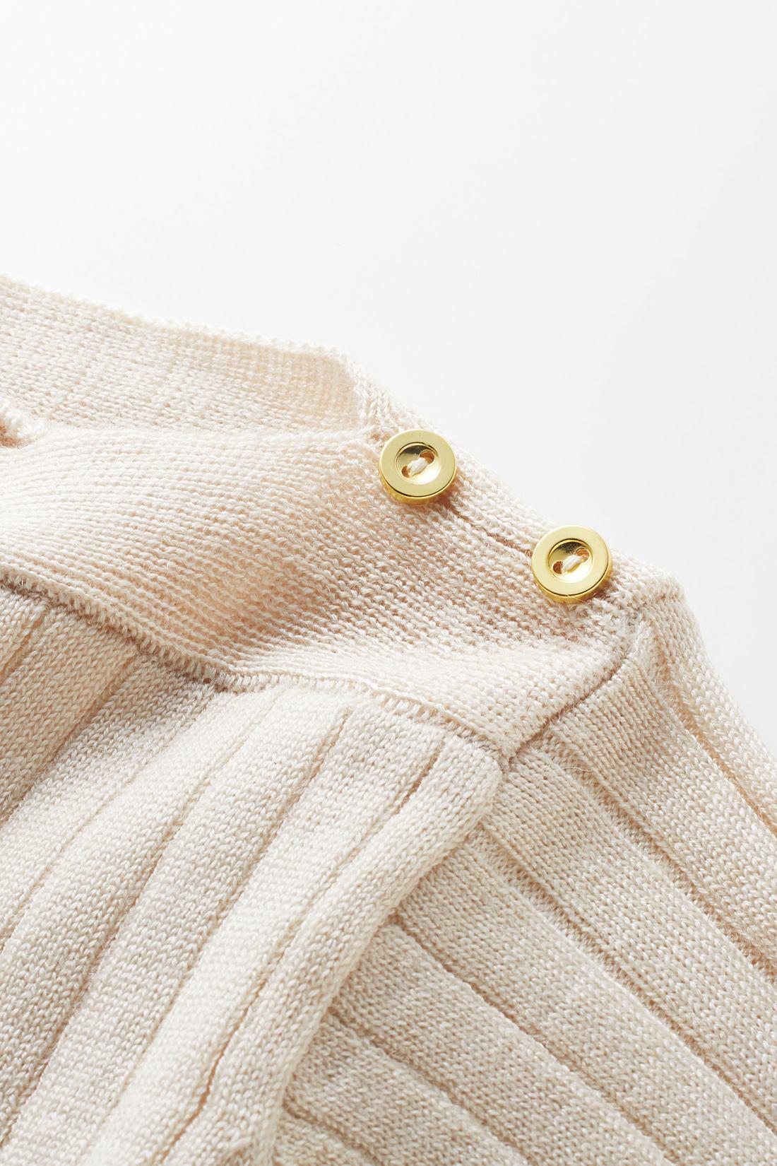 トレンドのボートネックに、金色のボタンがポイントに。