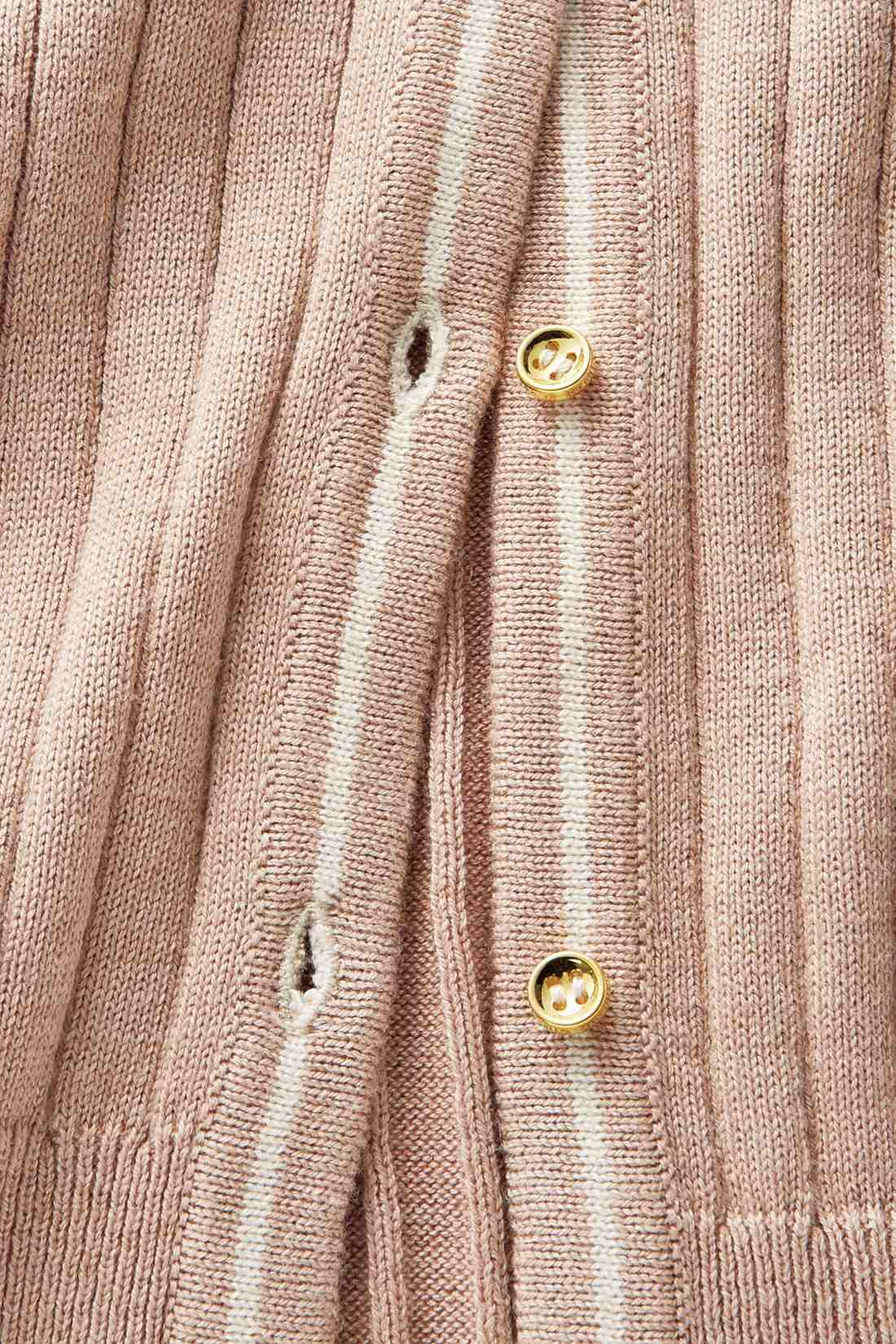 カーデの前たてに入れた配色のラインとゴールドボタンがほどよいアクセントに。