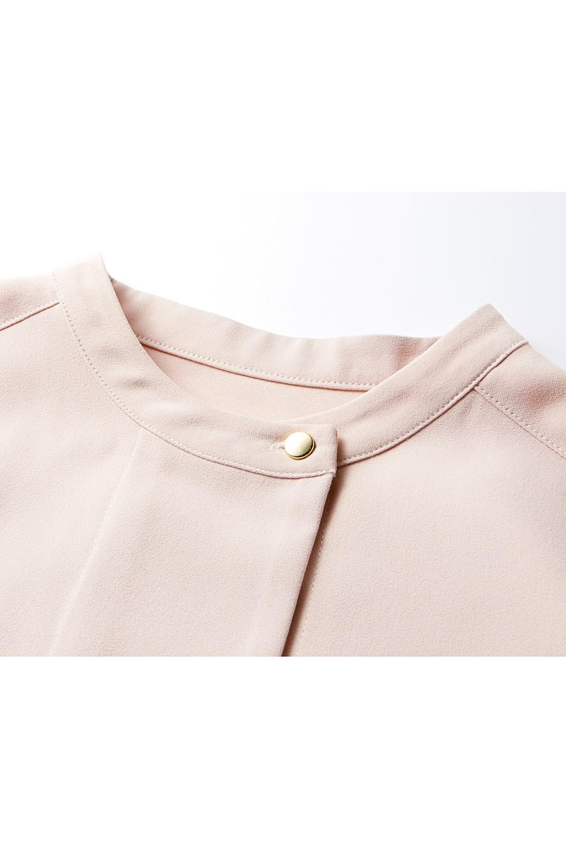 衿もとのゴールドボタンが上品な印象。