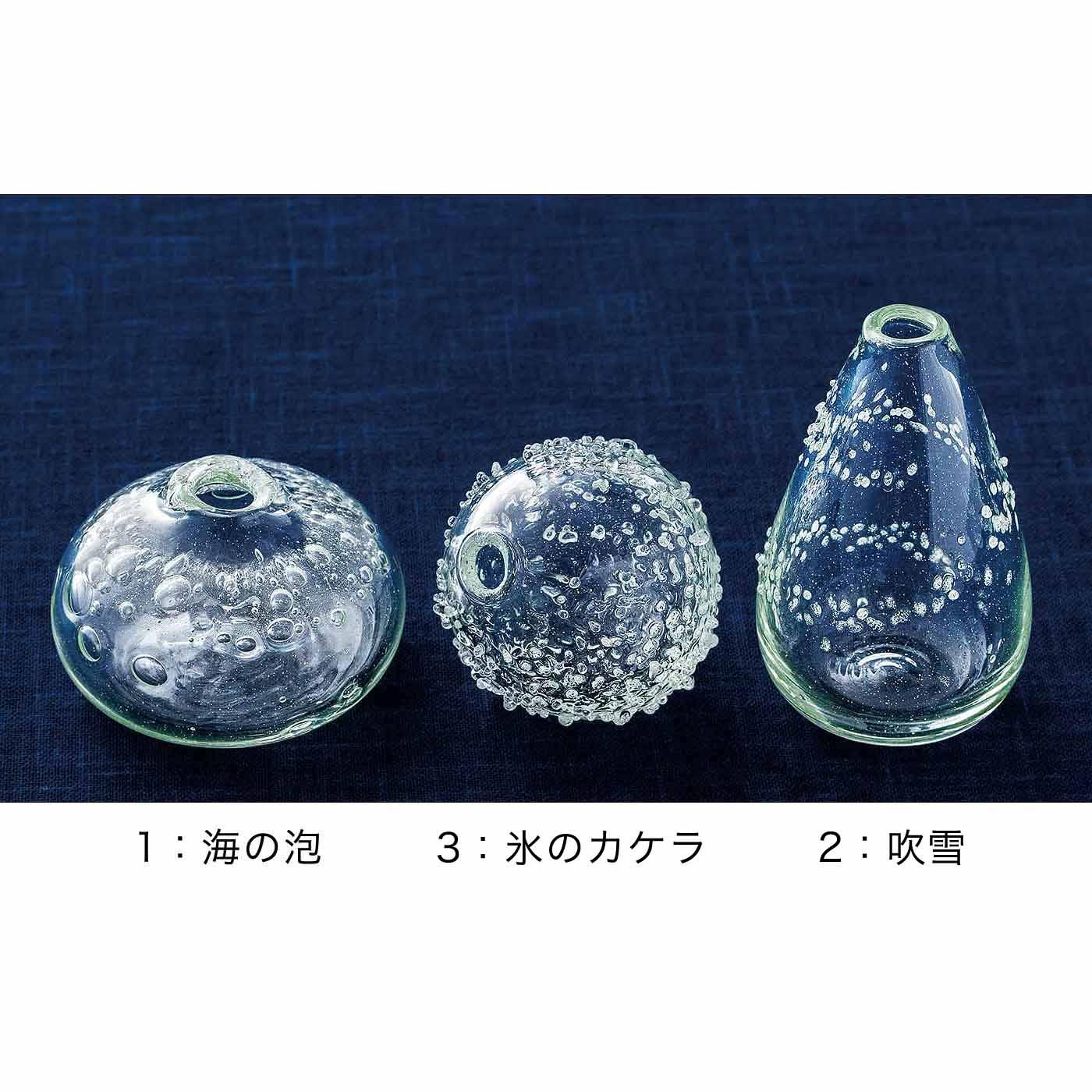海の泡:直径約7.5cm、高さ約4.5cm/ガラスの中の泡は美しく、おまんじゅうのような形が愛らしい。 氷のカケラ:直径約5.5cm、高さ約5.5cm/小さな氷のカケラをまぶしたようなデザイン。口が斜めについているのでユニークな生け方が楽しめます。 吹雪:直径約5.5cm、高さ約9cm/下から上にらせんを描いて雪が舞い上がる様子をデザインしました。しずくのような形が味アリ。