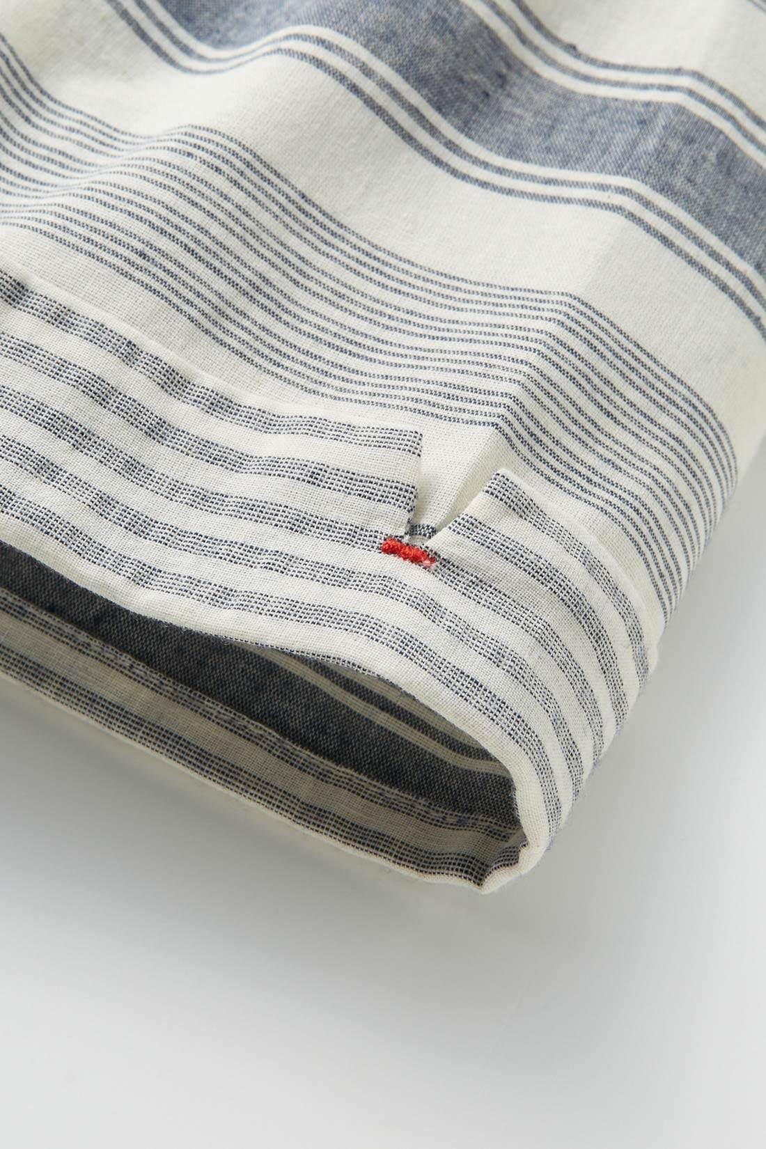 袖口はピッチの違うボーダー柄で、折り返し風デザインに。カン止めのカラーもおしゃれなポイント。
