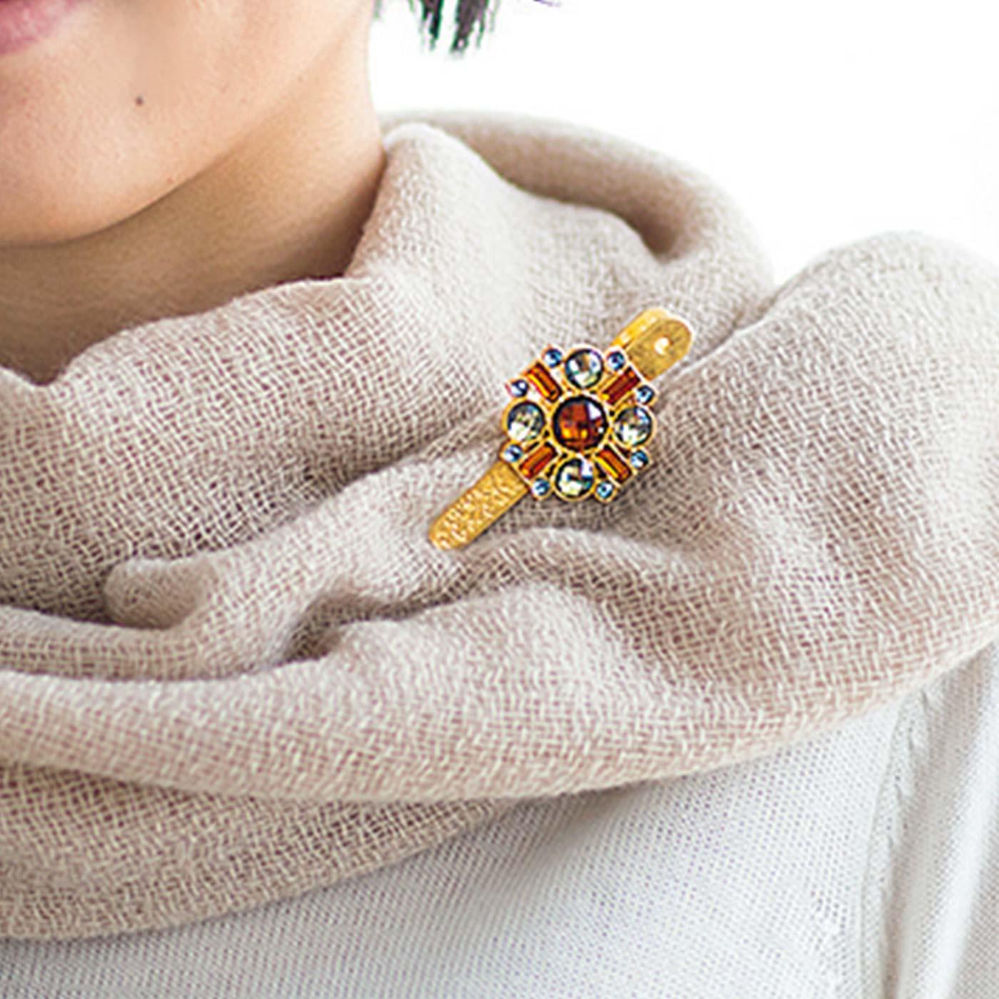 スカーフを留めて顔まわりを華やかに。