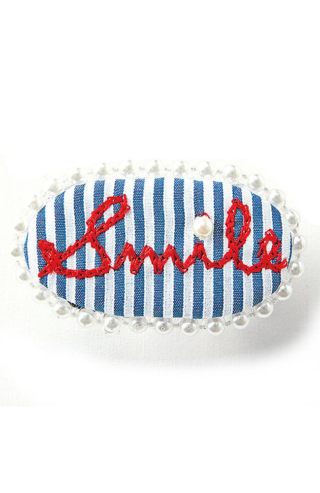 """上品なストライプに""""Smile""""の手描き風ロゴ刺しゅうで、気分もハッピー。パールの縁取りもキュートです。"""