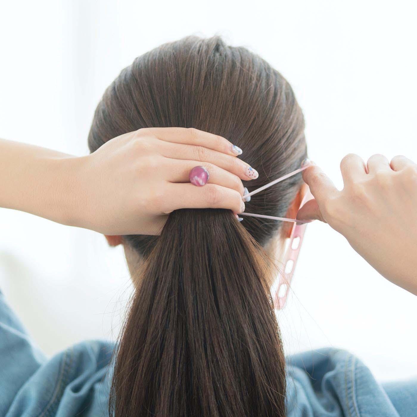 〔使い方はとっても簡単!〕髪をまとめてつかんでいるほうの指で球をはさみ、ヘアゴムをぐるりと1回巻き、いちばん大きな穴に通して固定します。