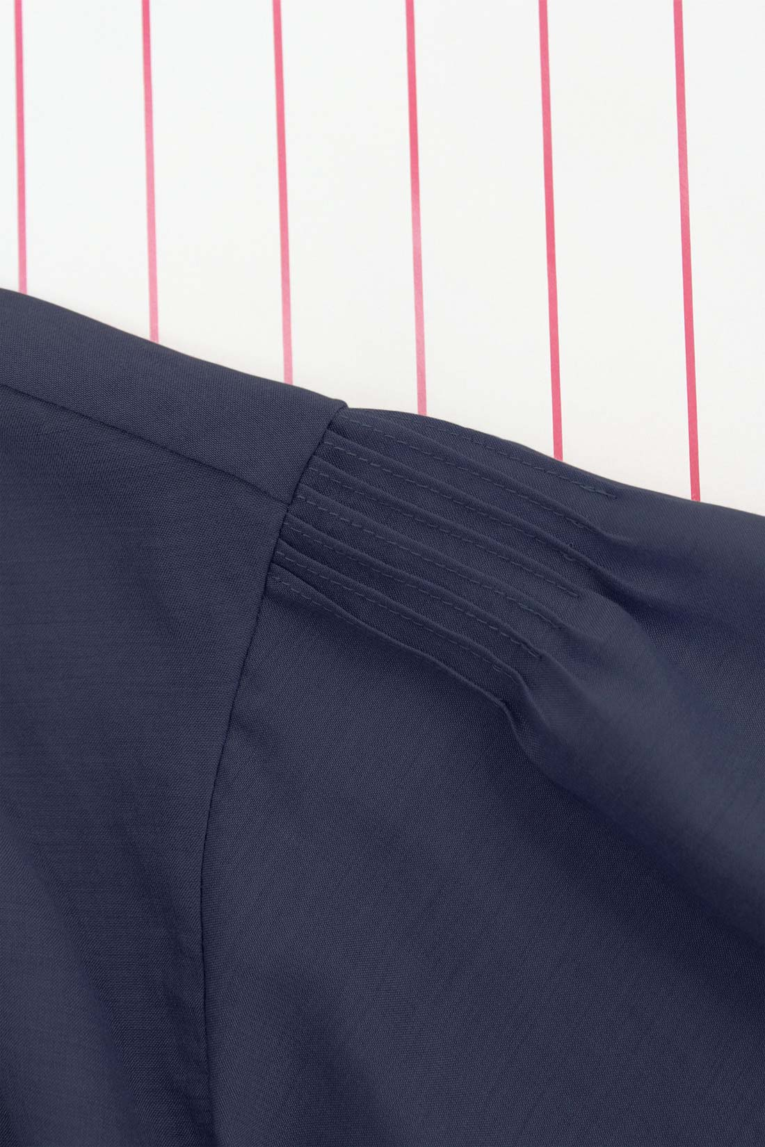 袖山のタックや前すそのデザインなどこだわりのディテール。