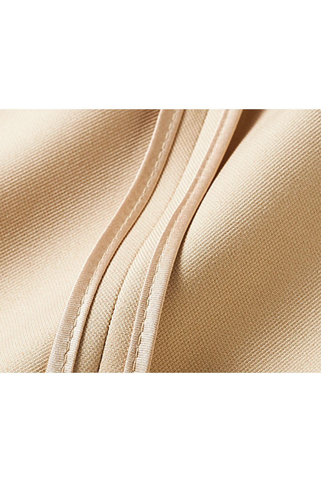 パイピング遣いで脱いでもきれいな印象 一枚仕立てのコートの裏は、縫い端を丁寧にゴールドサテンのテープでパイピング。ひらりと裏が見えた時や脱いだ時にも上質感が漂います。