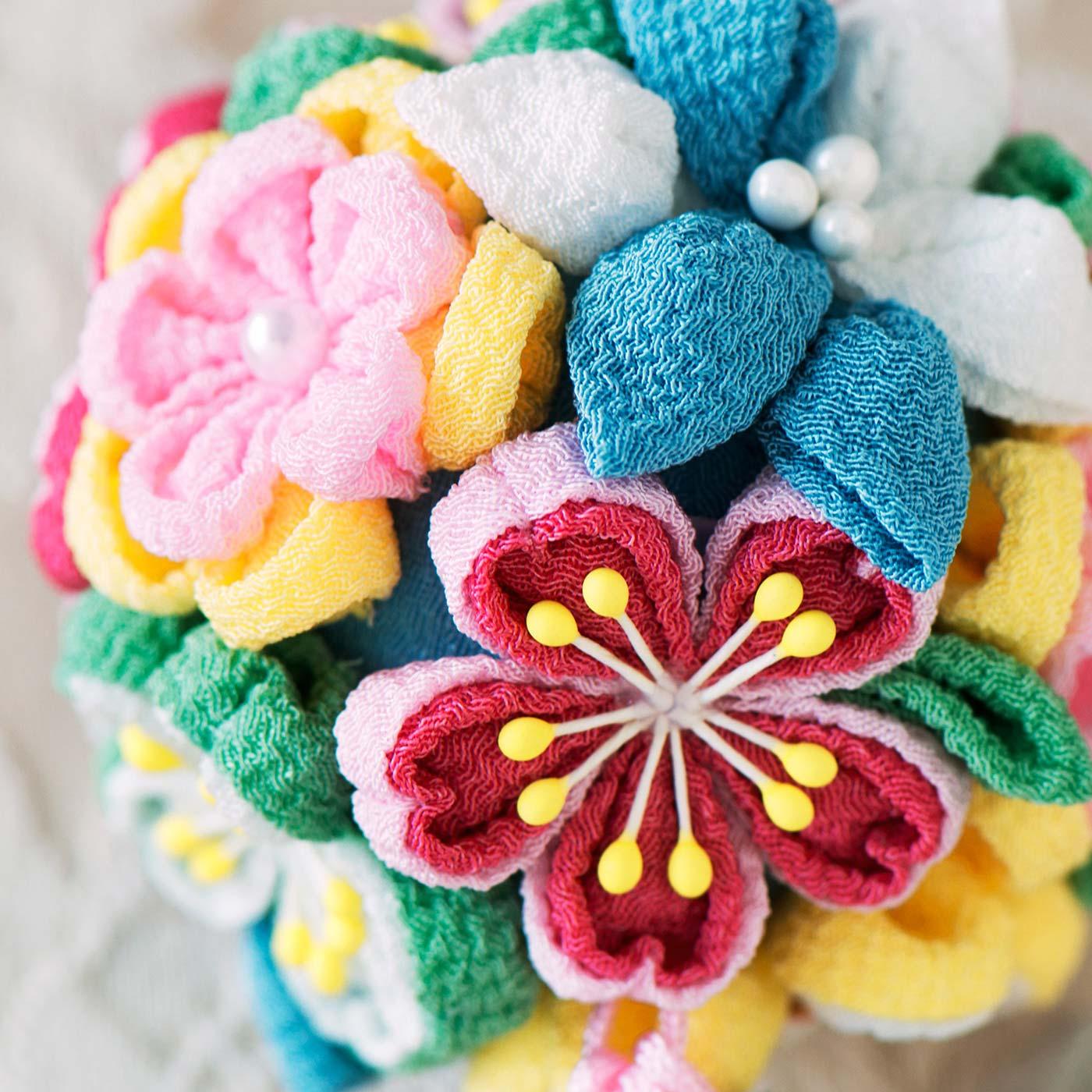 さまざまなお花をぎゅっと集めて、絶妙なバランスでレイアウト。つまみ細工の立体感が際立って、360度どこから見ても美しく迫力も満点。