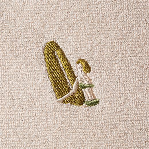 古いポスターをイメージしたサーフガールの刺しゅうがワンポイント。