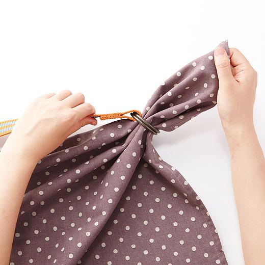バッグにするクロスを外表にしてふたつに折り、重ねたクロスの端を二重のリングに通す。
