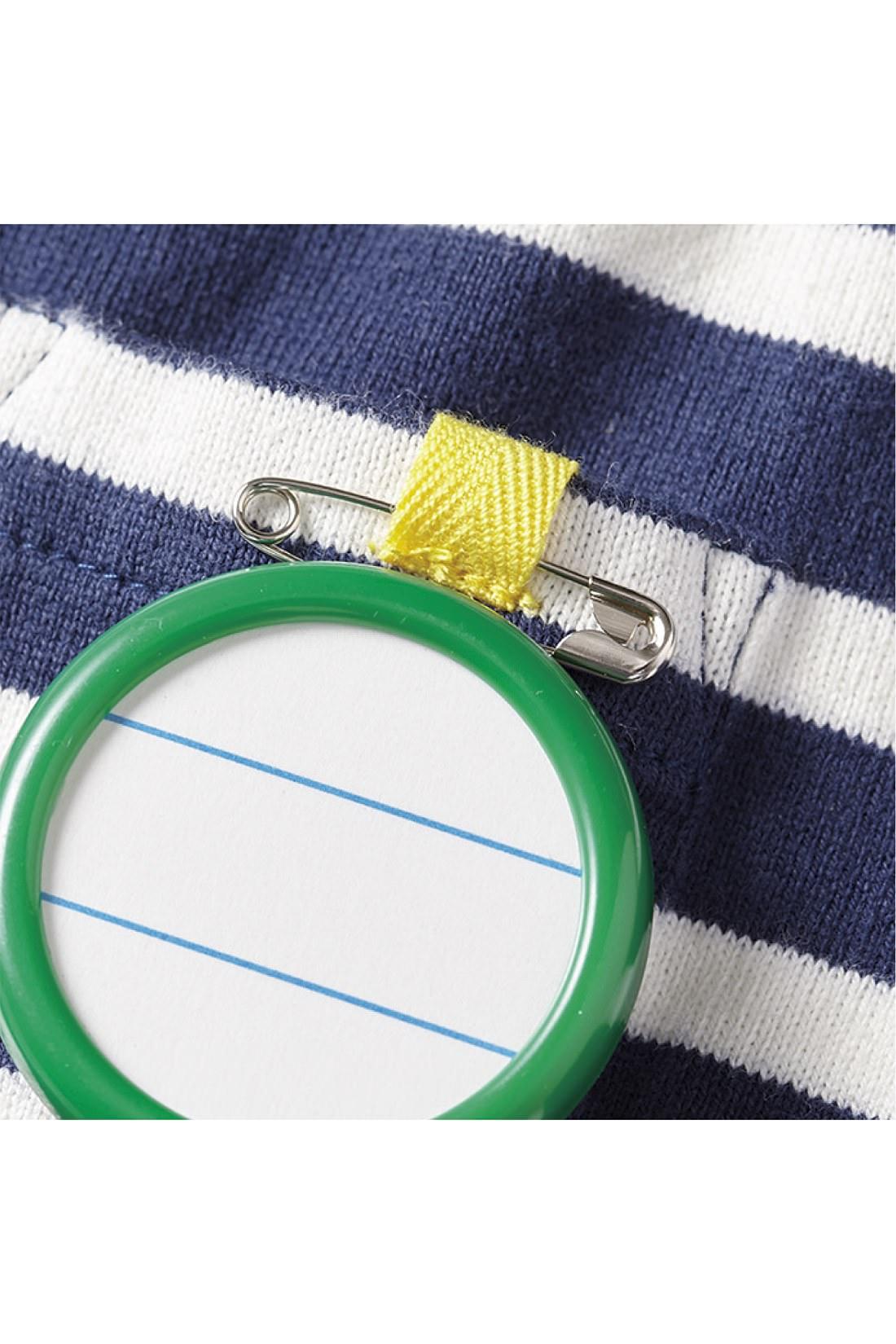 これは参考画像です。キッズトップスの胸ポケットには、ネームピンが通せるループタグ付き。