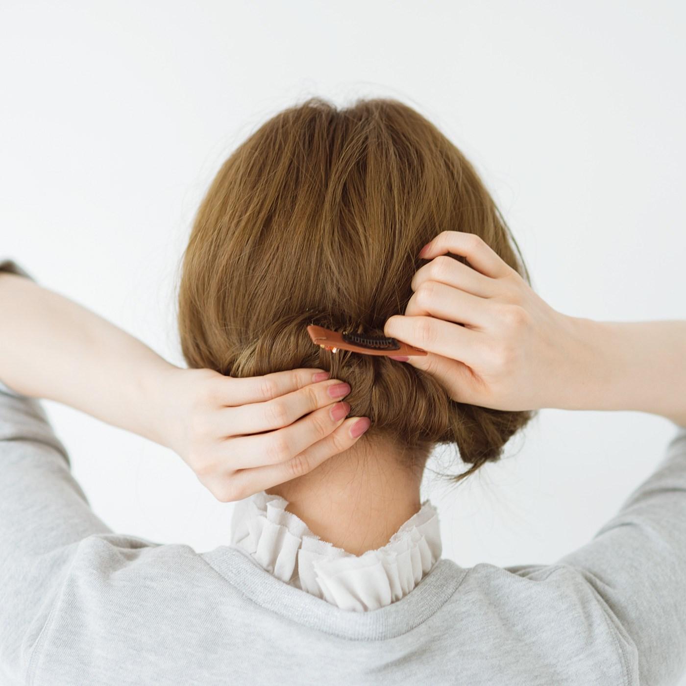 あらかじめ下の方で、ゴムで結んでおきます。毛先を上に向けて巻き込み、コームで髪をすくいます。
