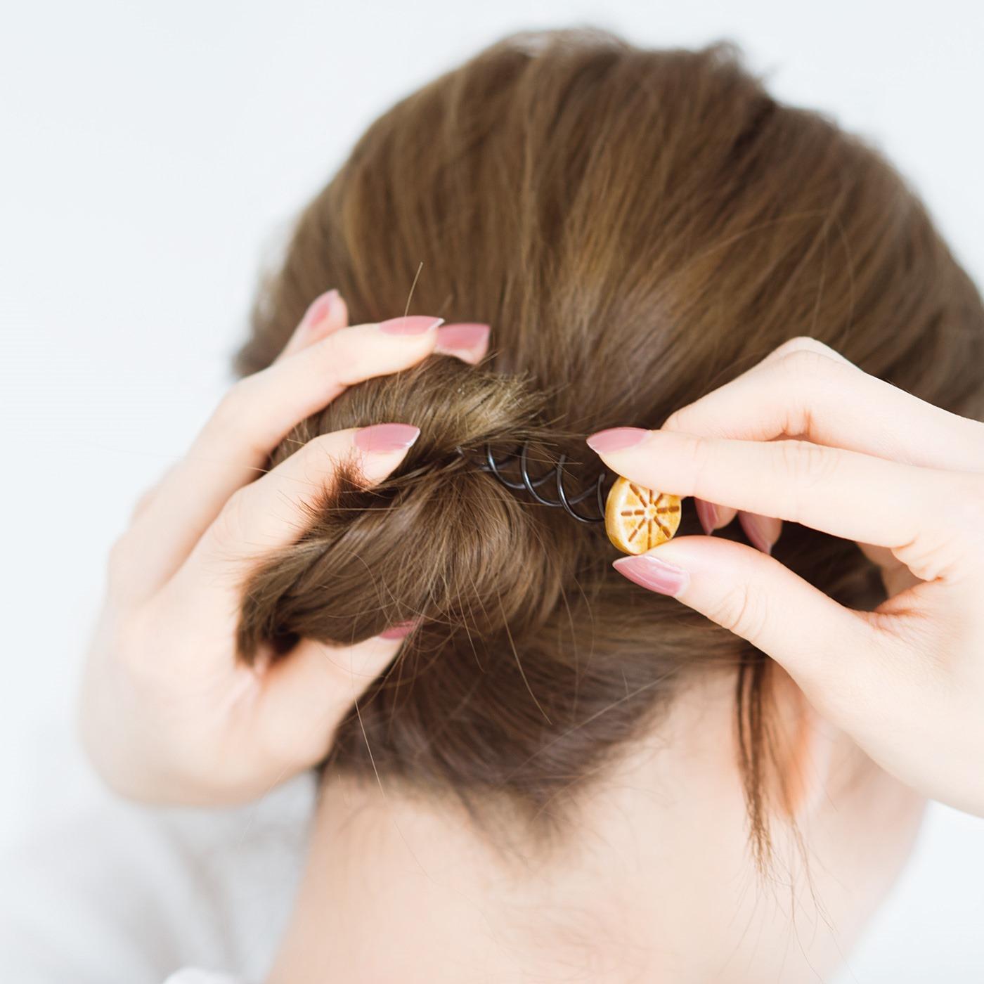 まとめた髪にピンをねじり込んでいくだけ。