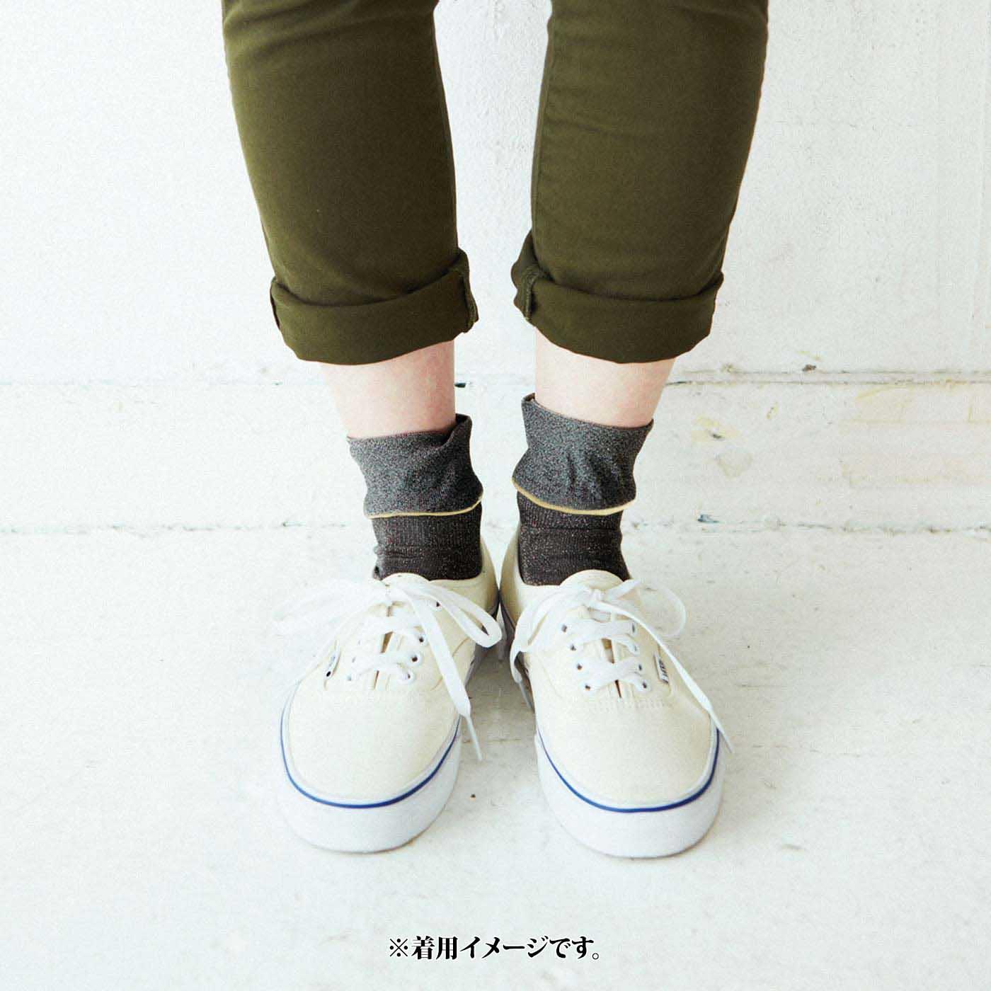 カジュアルなスニーカースタイルも大人っぽく。パンツには折り曲げではくのがおすすめ。