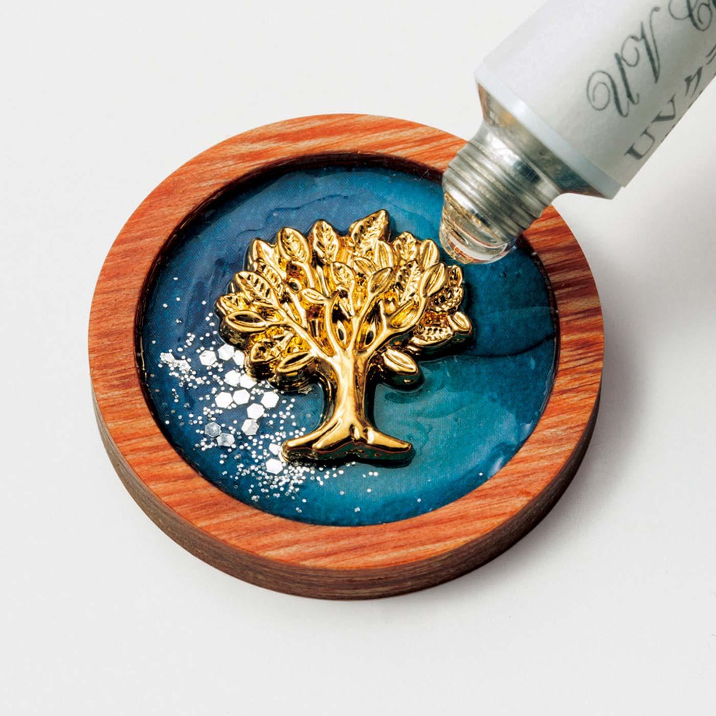 [UVレジンクラフト]人気の技法にチャレンジ。ボタンみたいな木枠にチャームなどを配置してUVレジン液を流し込み、紫外線で固めると完成。