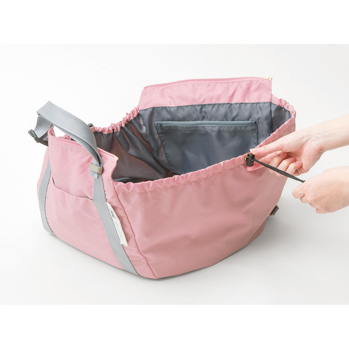 両サイドのひもでバッグをしぼり、上部のファスナーを閉めます。