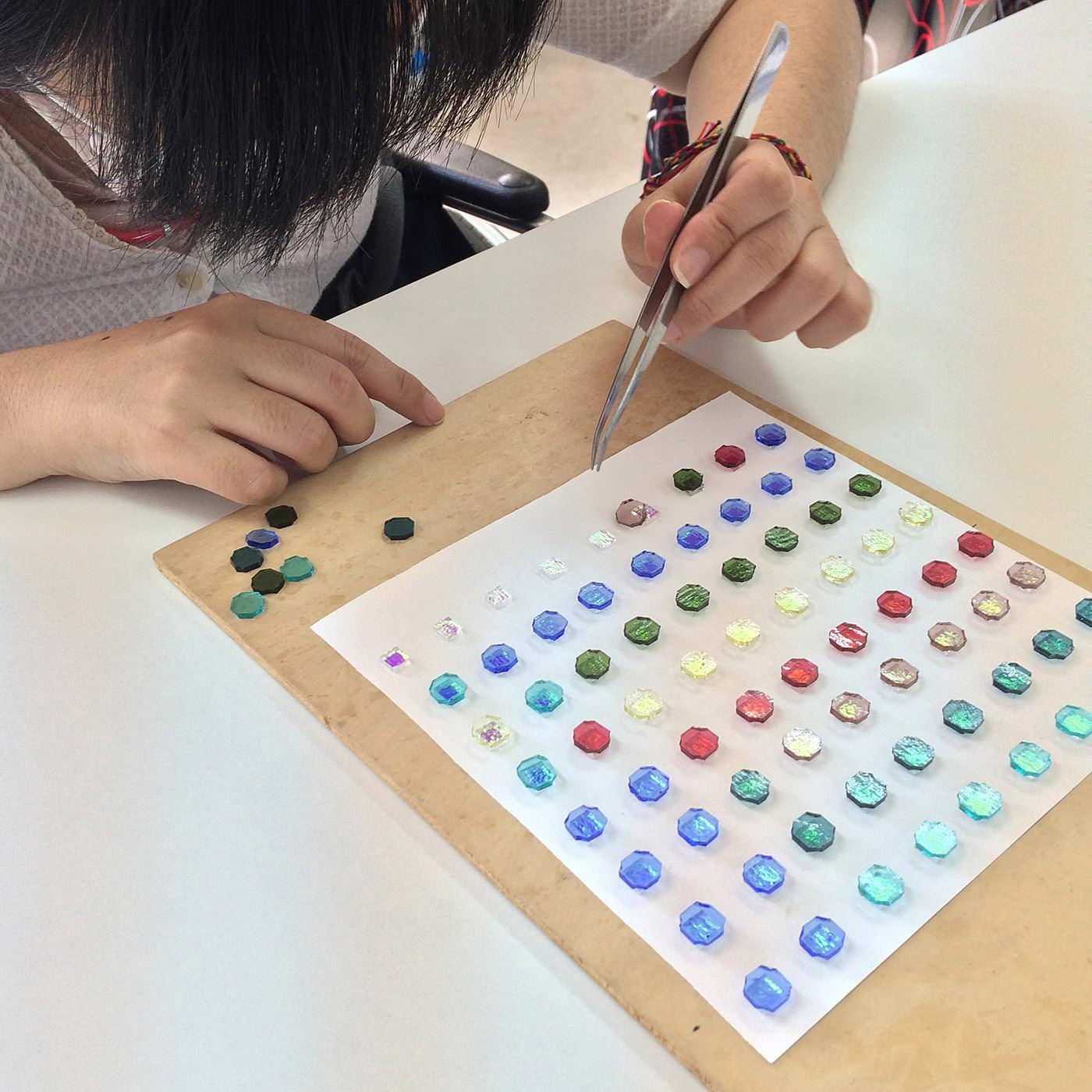 虹色のダイクロガラスの上に、色板ガラスをひとつずつ重ね、ピンセットを使ってていねいに並べます。