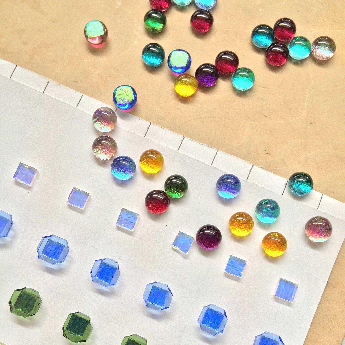 焼成前の角ばったガラス(手前)と、焼成後のころんとした丸いガラス(奥)。焼成(しょうせい)前のガラスは、きれいな丸い形に仕上がるように、角はカットされています。