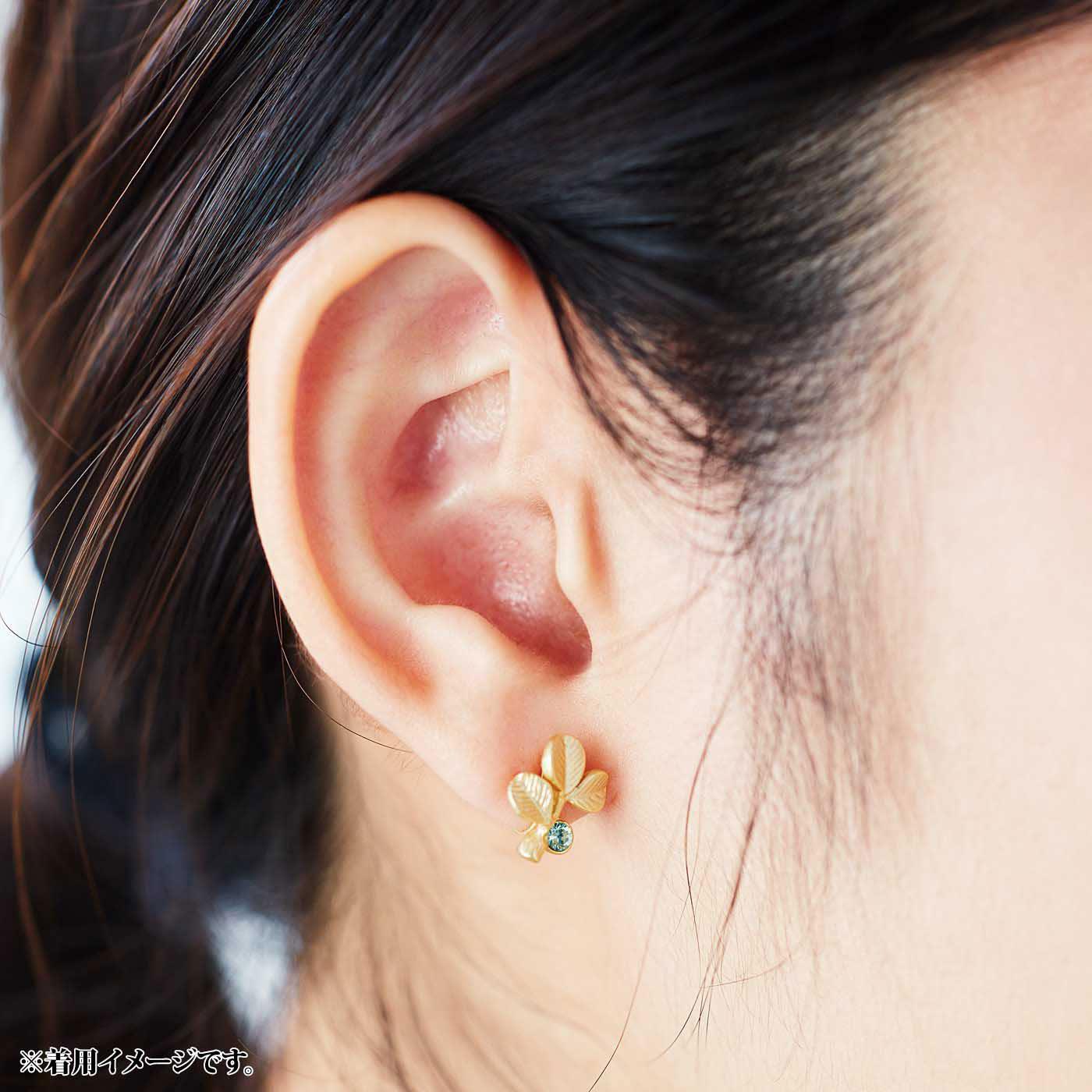 右耳はおそろいのスワロフスキーをあしらったアシメトリーなデザインのピアスまたはイヤリング。