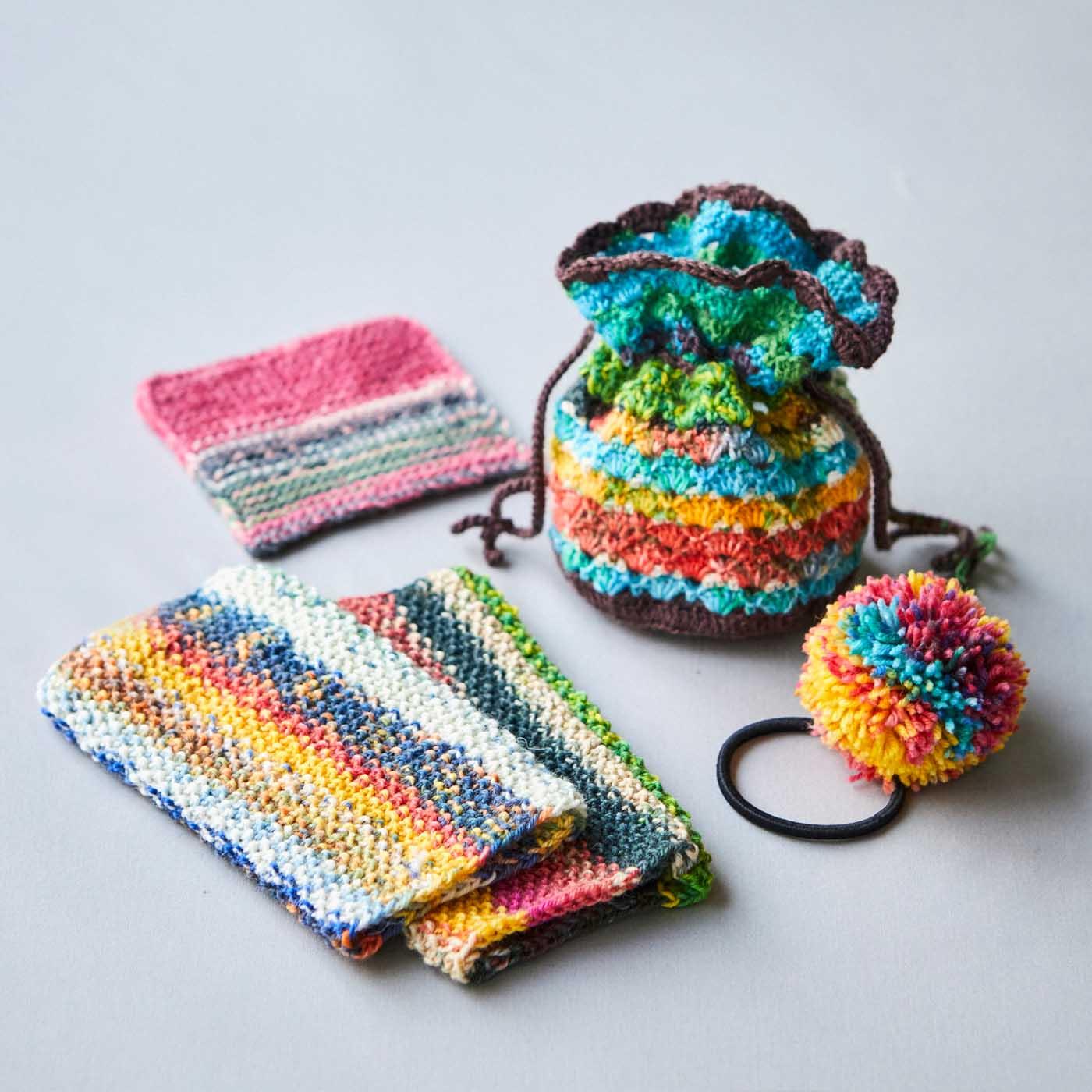 プレゼントの毛糸玉で作った作品例。1玉でボンボンやコースター、2玉でリストウォーマー、3玉できんちゃくに。